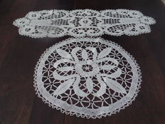 One round and one oval shaped doily made from Bruges bobbin lace.