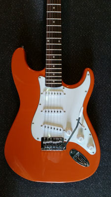 Volcano stratocaster model in the colour orange with stand, strap, bag, cable, picks and tuner