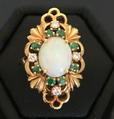 18kt yellow gold ring centred with an opal cabochon surrounded by emeralds and diamonds.