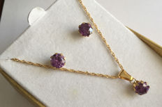 18k gold set, composed of earrings in stud style with amethyst gemstones in prong settings, and matching pendant with chain.