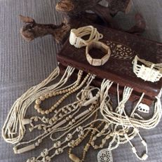 Fifteen horn or bone jewellery in a wooden box.