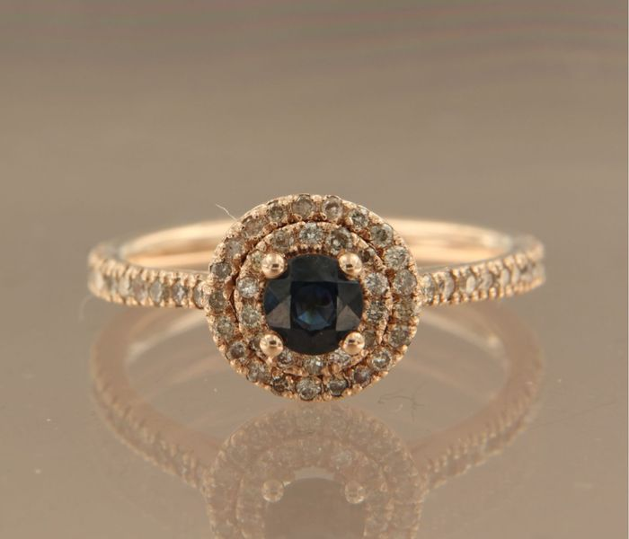 14k rose gold entourage ring, set with a central brilliant cut sapphire of approx. 0.50 carat in total and with 56 brilliant cut diamonds of approx. 0.33 carat in total ***NO RESERVE PRICE***