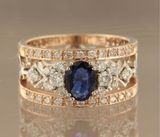 Bi-colour band ring of 14 kt, set with a central oval cut sapphire and 44 brilliant cut diamonds of approx 0.66 ct in total as entourage – Ring size: 17.5 (55)