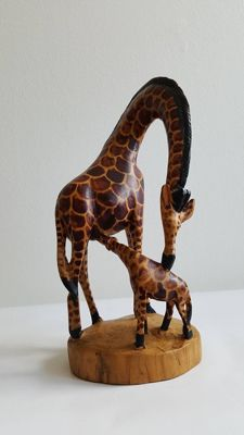 Hand-carved wooden giraffe with baby giraffe on console, in brown/beige colour.