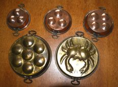 Four antique brass flat pans for escargots and a pudding shape