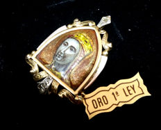 "Pendant in 18 kt yellow gold with details in silver and fired enamel. It represents The Virgin of Montserrat (""La Moreneta"")"