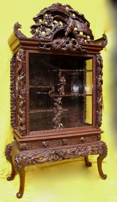 A very decorative finely carved fruitwood display cabinet, richly carved with all sorts of Japanese ornaments - Japan - circa: 1920