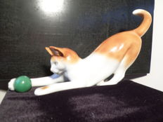Vintage porcelain cat playing with a green ball