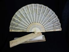 A folding fan with fitted box - carved polychromed bone and silk with gilt motifs and paillettes - Spain - circa 1900