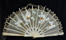 A carved bone and painted organza folding fan - with lace border - Spain - circa 1900