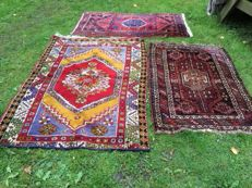 Two hand-knotted rugs, with a third hand-knotted rug for free.