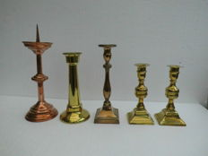 Four brass and one copper candlestick.