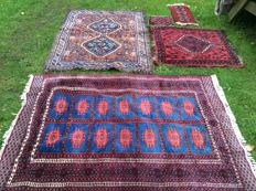 Two hand-knotted carpets, with three additional, complimentary, hand-knotted carpets.