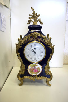 Porcelain fireplace/table clock decorated with inset gold decor, very fine.