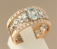 14 kt bi-colour white and rose gold channel ring set with a central blue topaz and an entourage of 34 brilliant cut diamonds of approx. 0.62 ct in total, ring size 17.5 (55)