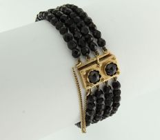 14 kt clasp set with a rose cut garnet, on a four-row garnet bracelet with a safety chain.
