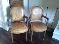 A pair of Louis XVI style arm chairs with leather upholstery, 20th century