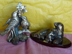 Two furniture pieces - One in silver laminate with mark by Alfonso Lucchese of a pair of birds placed on a vine while pecking grapes --one in silver coloured metal on a wooden oval base made and signed by