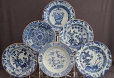 Collection of six deep plates with decoration of different attributes in a floral landscape - China - Qianlong period (1735-1796).