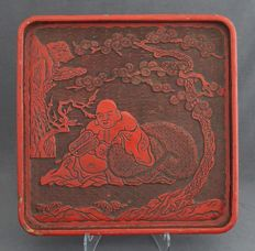 Lacquer, square tray with Happy Buddha with money bag under a pine tree - China - early 20th century.