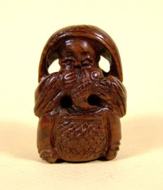 A boxwood 'katabori netsuke' of a seated man holding a fish - Japan - Meiji Period (1868-1912)