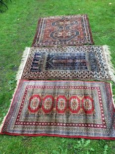 Two, hand-knotted rugs with an old, Persian carpet for free.