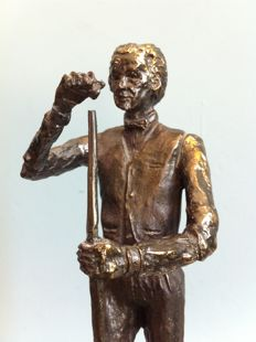 Bronze sculpture of a billiard player chalking his cue