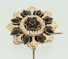Rose gold brooch set with rose cut garnet, with a safety chain.