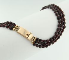 14 kt rose gold clasp on a three-strand garnet necklace
