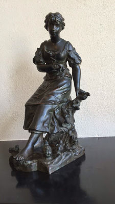 A bronze statue of a seated lady feeding chickens - ca. 1900