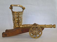Large and heavy decorative cannon on a gun carriage and a measuring cup / measuring bucket