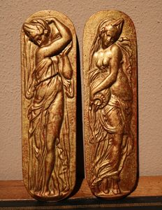 Two gold-plated antique cast iron wall plaques in relief