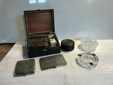 Large lot of smoking objects  - a machine to roll cigarettes - 2 silver cigarette holders- 1 smoking Pot  - 1 glass cigarettes display - 1 ashtray - 1 silver plated tobacco jar - 5 cigarettes holders