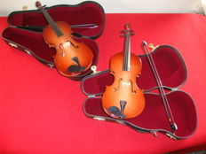 Two (mini) violins in a case, including bows. Stored in a showcase for years. Like new. Unique, handmade.
