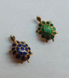 Pair of 18 kt gold brooches.