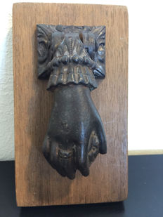 Robust cast iron door knocker in the shape of a hand with sphere, first half of the 20th century.