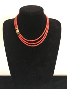 A three-strand red coral necklace with 14 kt gold clasp