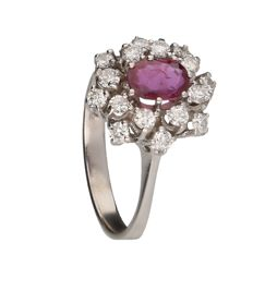 White gold 14 kt rosette ring set with 16 brilliant cut diamonds of 0.64 ct in total and an oval cut ruby. Ring size 17.75 mm