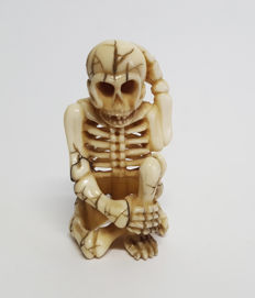 Ivory netsuke depicting a seated skeleton, signed – Japan – 1868-1912 (Meiji period).