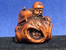 A palm wood Netsuke of Shoki and Oni – Japan – circa 1900