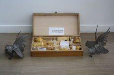 """Lot: Wooden Case containing 8 bird calls """"The song of the birds"""" / Two fighting cocks in chiselled silvered metal - Mid 20th century - France"""