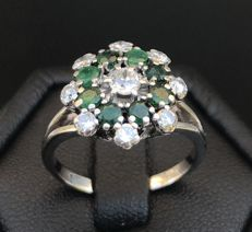 Marvellous ring in the shape of a flower in 18 kt grey gold with emeralds of 0.8 ct and Tope Wesselton diamonds of 0.55 ct and VS.