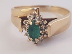 Yellow gold ring with a Colombian emerald in the centre surrounded by 8 diamonds.