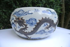 Cachepot with a cloud décor in blue, two dragons in dark brown relief on a crackleware base – China – 19th century.