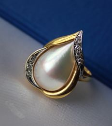 14 kt. Gold ring forged with a special goldsmithing technique and a very large South Sea Mabe pearl of the best quality surrounded with diamonds.