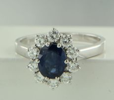 18 kt white gold entourage ring, set with oval-cut sapphire and ten brilliant-cut diamonds, ring size 17.25 (54)