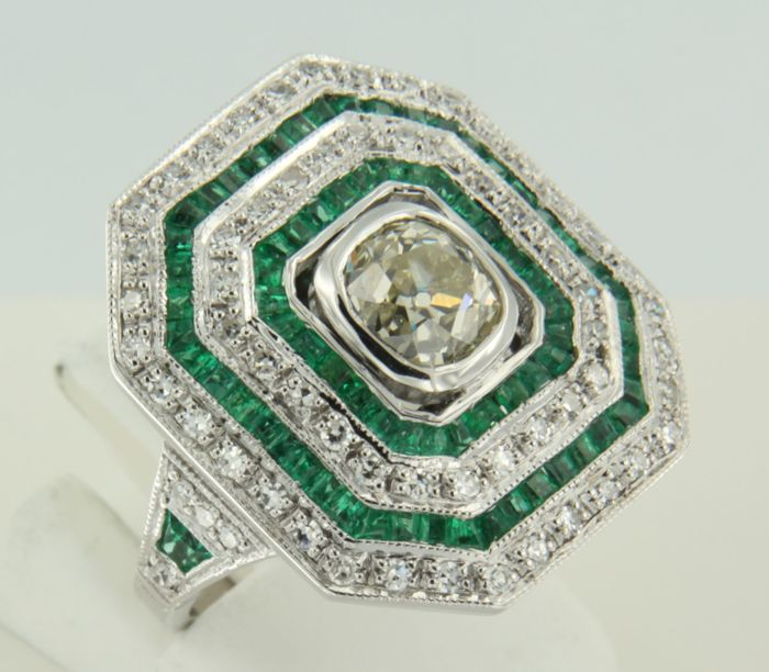 14 kt white gold ring in Art Deco style with a central 1.24 ct cushion Bolshevik diamond, surrounded by 78 carré and tapered cut emeralds of 2.14 ct and 60 single cut diamonds of 0.54 ct