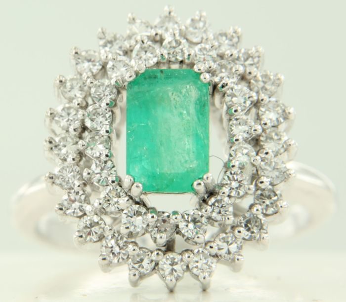 18 kt white gold entourage ring set with a central emerald cut emerald and 42 brilliant cut diamonds, in total approx. 1.17 carat, ring size: 18.5 (58)