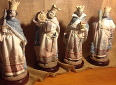 Four Lladró porcelain figures. They depict the four kings of the Spanish deck