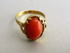 Gold ring with oval, cabochon cut red coral.